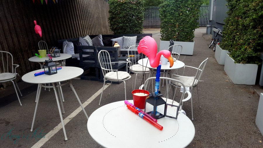 Image of Blog at the beach event decor - flamingos, bubbles and lantern on a white table
