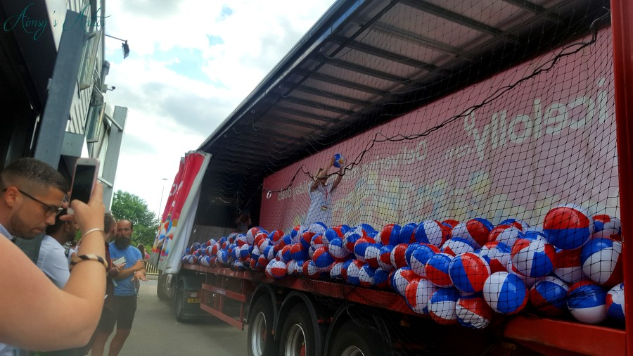 Image of a Girl holding up the winning beach ball in a lorry filled with beach balls at Ice Lolly's blog at the beach event