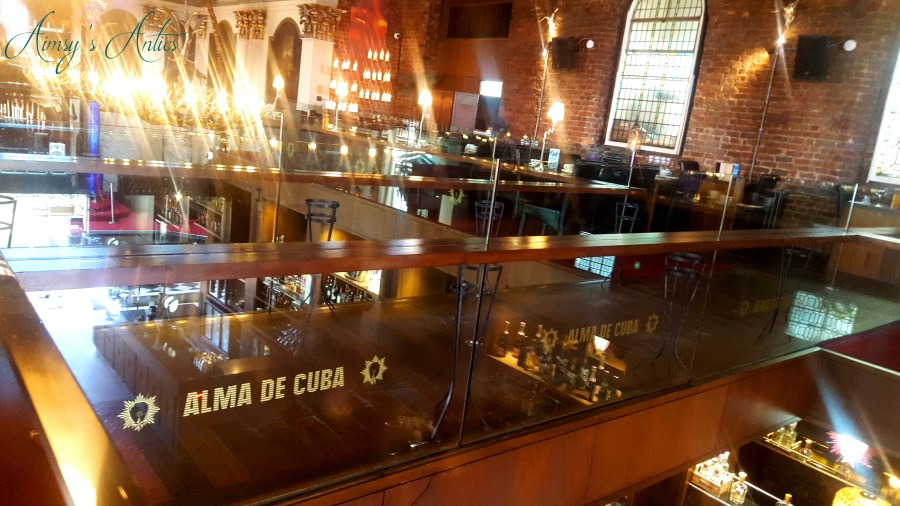 Inside Alma De Cuba with table and chairs. Lights flared