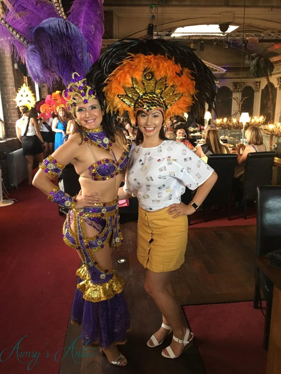 Samba dancer posing with other woman wearing headdress