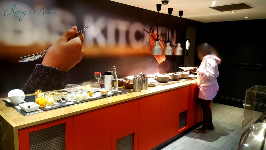 Image of Ibis Hotel Leeds cooked breakfast bar with a woman filling her plate.