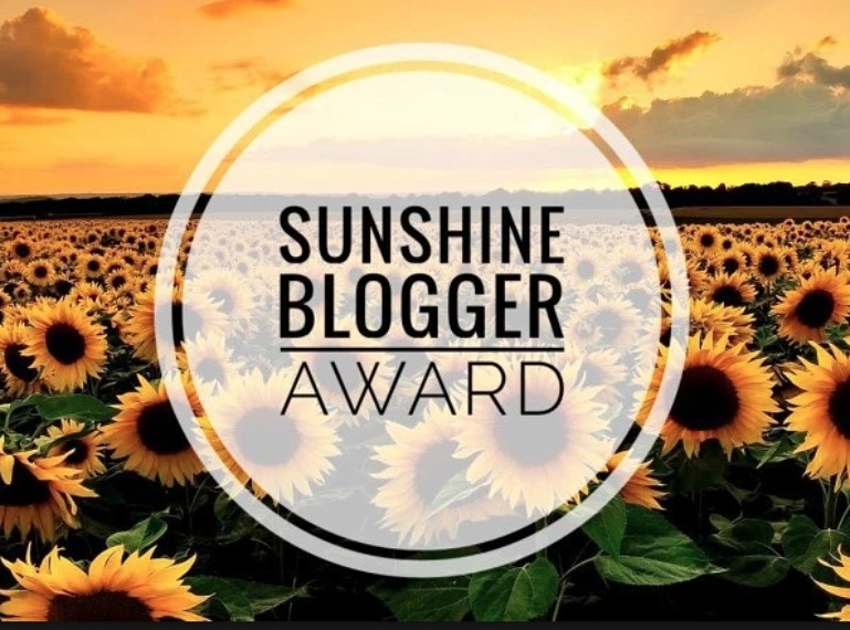 Image of the Sunshine blogger award, sunflower field in the background.