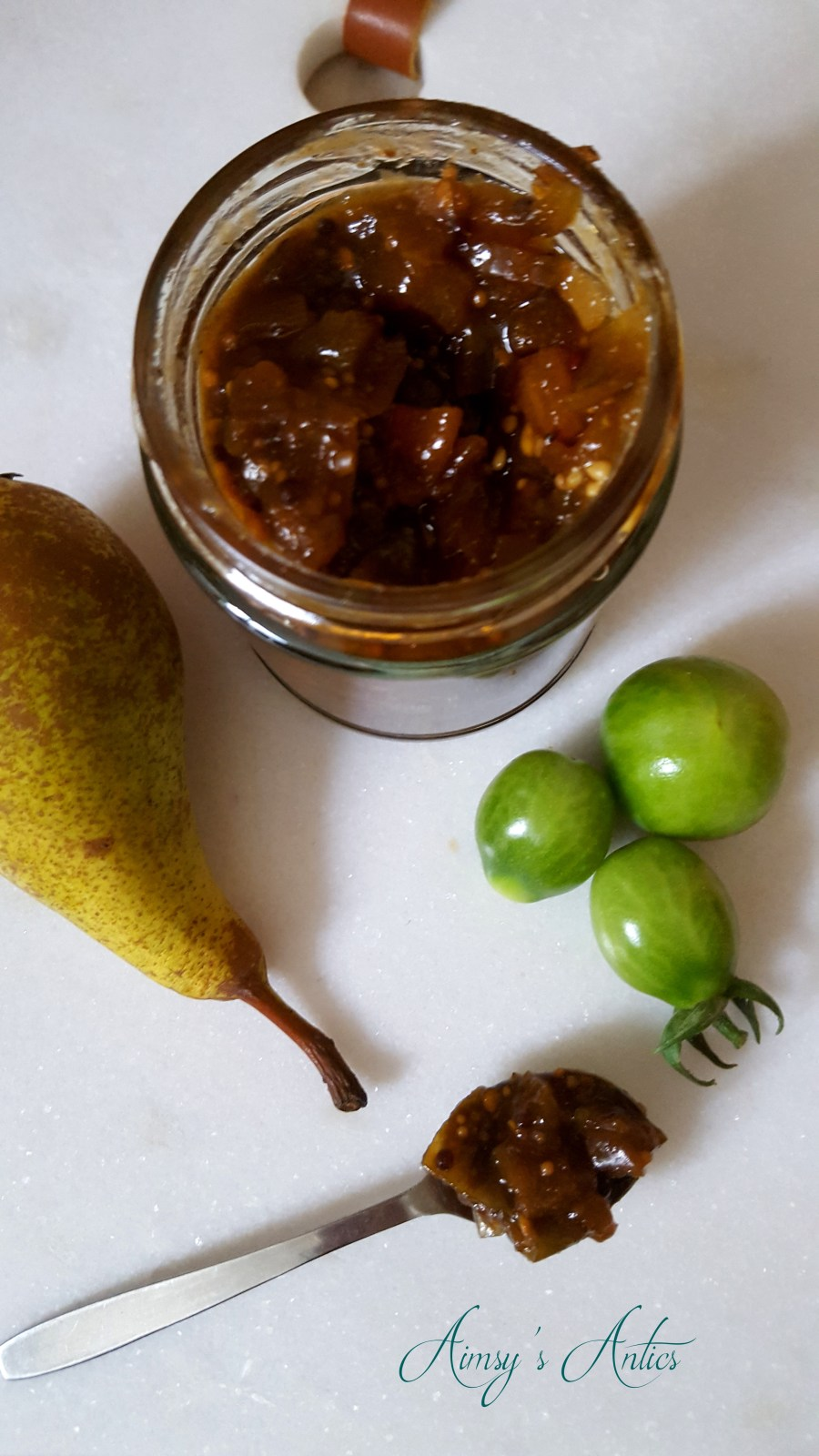 Image of tomato and pear chutney in a jar with a pear and green tomatoes around the jar. Also a teaspoon of chutney is in the shot