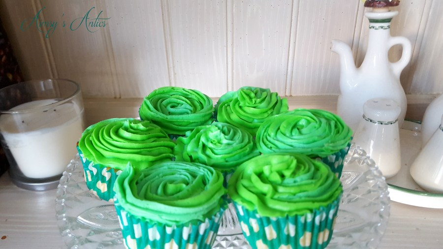 Image of  7 cupcakes on a clear crystal cake stand, with green buttercream icing. Candle and salt, pepper and vinegar pots in the background.