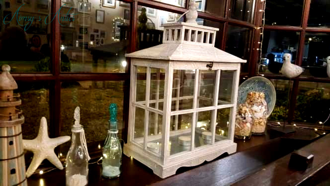 Image of a window with various items decorating it, including a large wooden lantern, white starfish and bottles with white sand in. Fairy lights up one side of the window