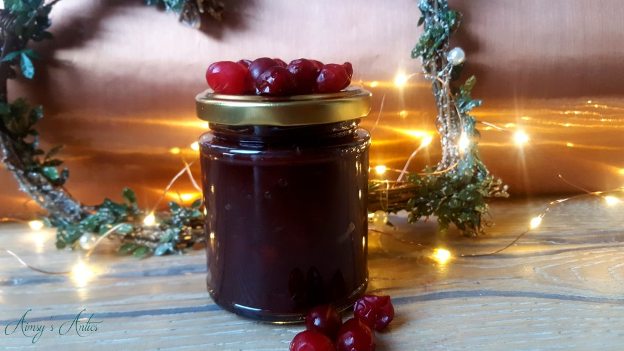 Image of a jar of cranberry and red onion relish. Cranberries adorn the top of the jar, with a handful in front. Heart shaped Christmas wreath, and fairy lights in the background