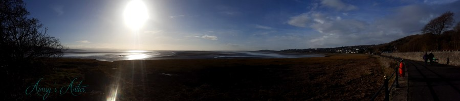 Panorama view of Grange-over-Sands promenade area, with the sun in the top left corner.