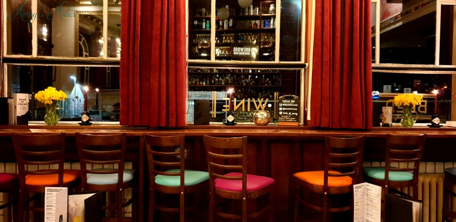 The Bank of Conwy wine bar inside - multicoloured bar chairs lined up against the window
