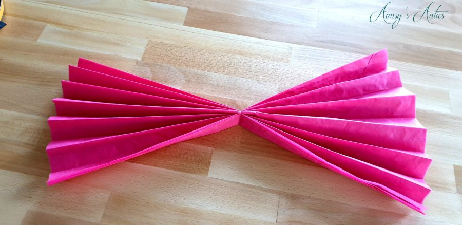 Pink tissue paper folded and tied in the middle resembling a bow.