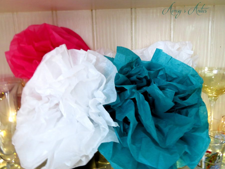Large white, pink and teal tissue flowers displayed in cocktail glasses