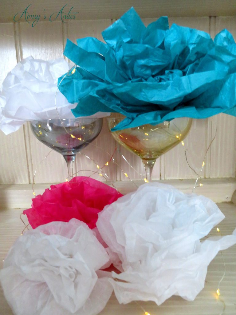 Various coloured tissue paper flowers in cocktail glases with small lights