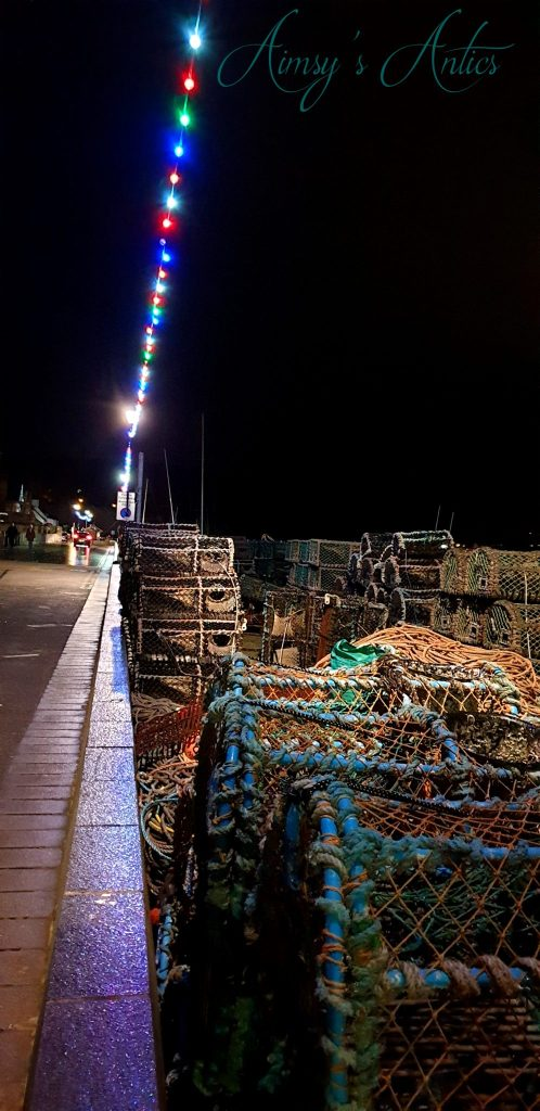 Night at the quayside of Conwy. Multicoloured string lights shine down on lobster pots