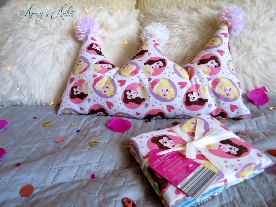 Disney fat quarters bundle in front of the made crown shaped cushion.