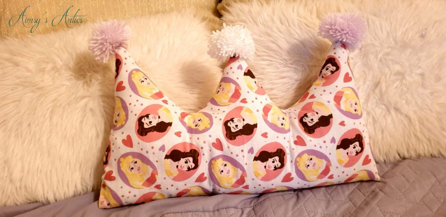 Crown shaped cushion with pink and white pom-poms, infront of two white fur cushions.