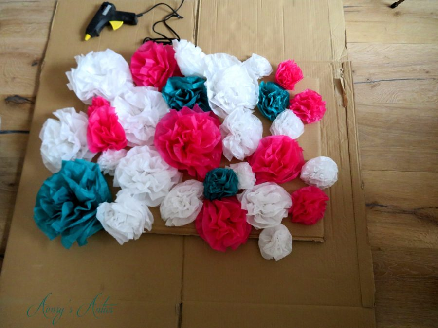 Paper flowers arranged on a piece of cardboard. Glue gun in shot, and the carboard 'wall' is on top of a larger peice of carboard.
