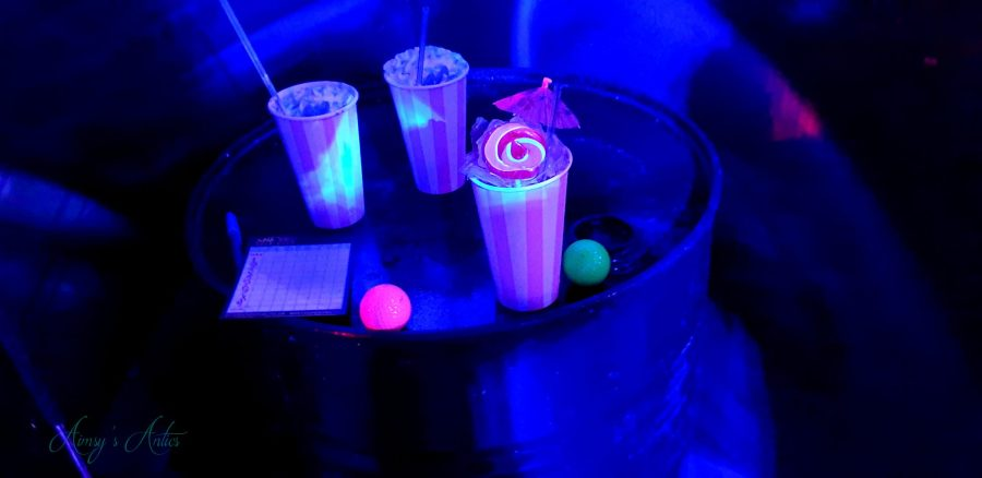 Cocktails on an oil drunk in semi-drkness and neon lights illuminating