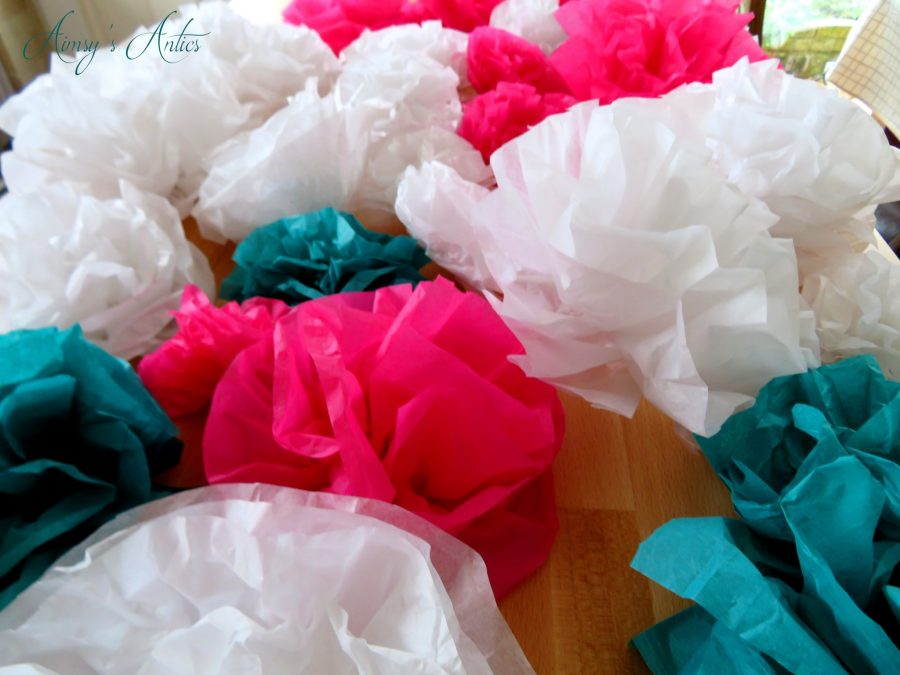 Several Paper flowers on a counter in white, pink and teal colours. Varying in size.