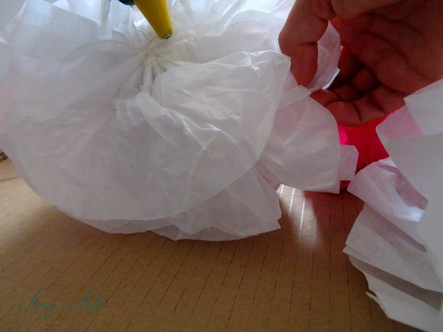 Hot glue gun being used to stick a tissue paper flower to carboard