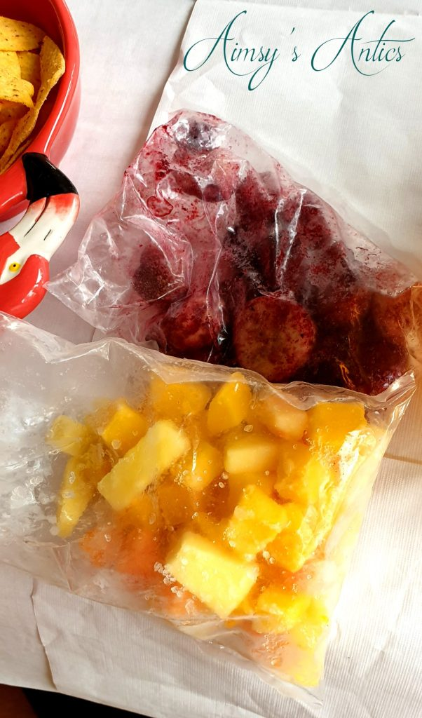 Two bags of frozen fruit, one yellow in colour and the other red in colour