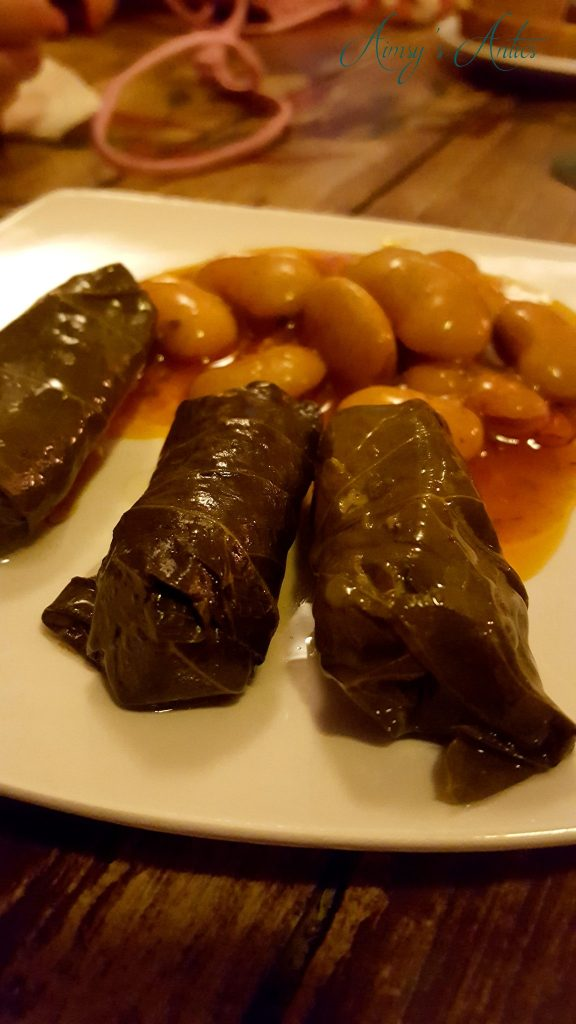 Stuffed vine leaves and giant beans on a plate