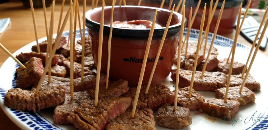 Steak bites with chilli sauce served on a plate with wooden cocktail sticks in them