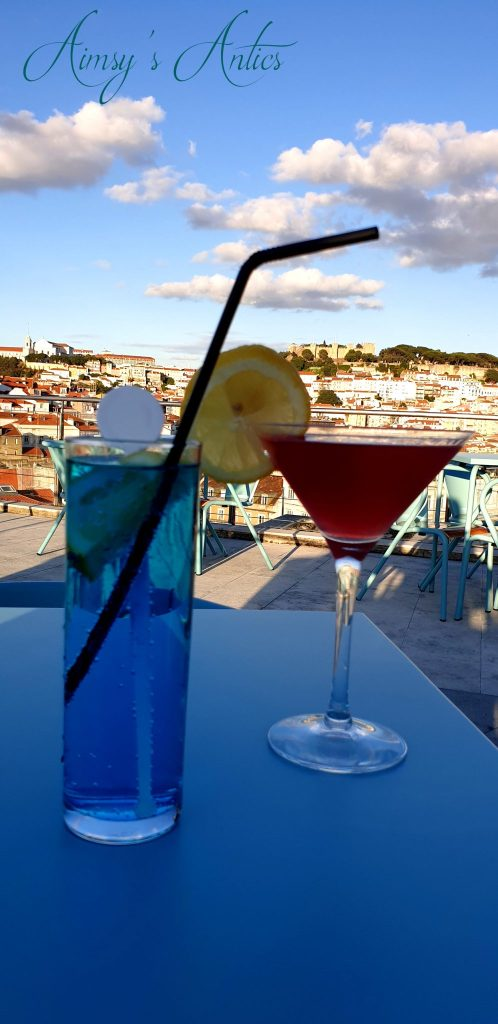 Two cocktails with the view of Lisbon behind