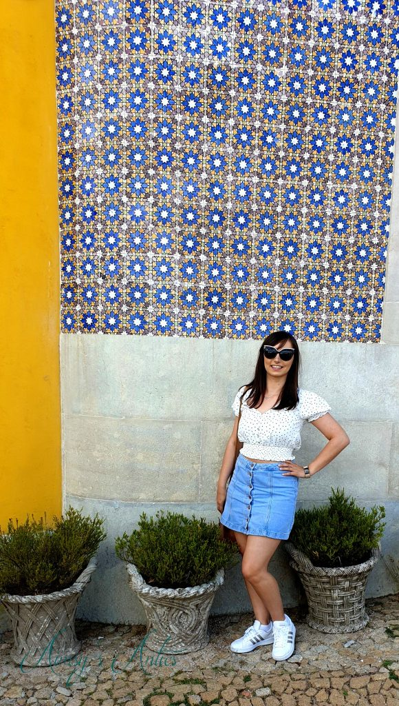 Woman stood infront of a yellow wall with blue Portuguese tiles at Pena Palace, Sintra