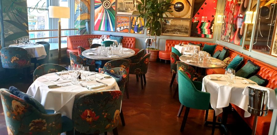 Brightly pattern walls with tables and chairs contrasting at The Ivy Leeds