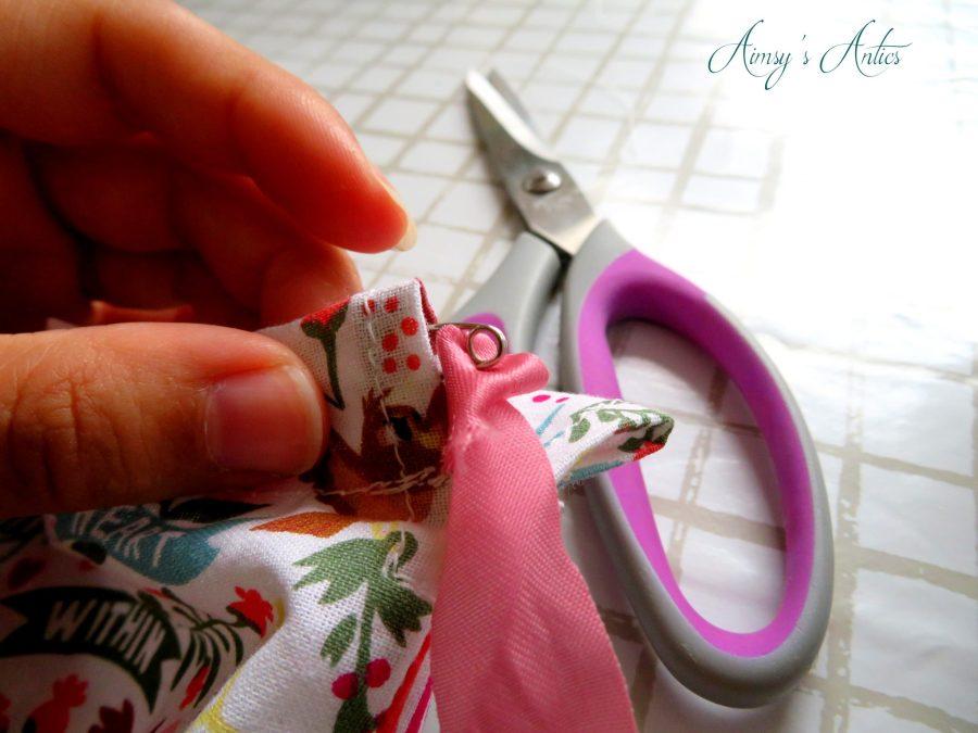 Ribbon being threaded into drawstring bag