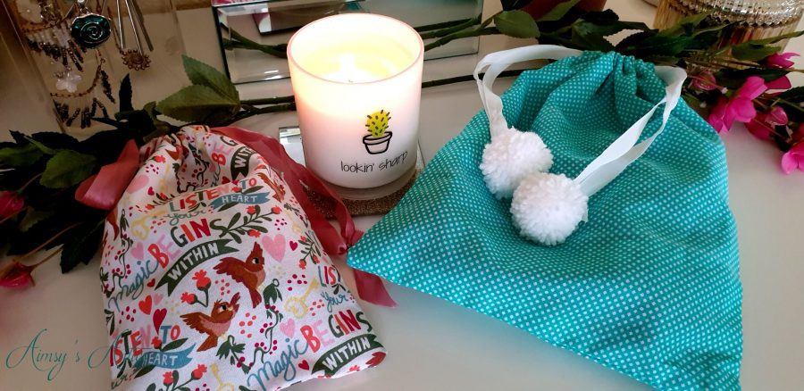 Two drawstring bags with a lit candle between them