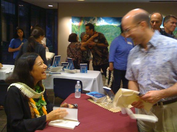Lurline McGregor autographs copies of her new book, Between the Deep Blue Sea and Me