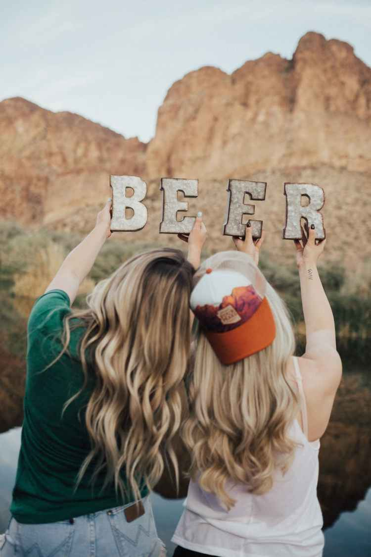 selective focus photography of two women holding beer cutout letters