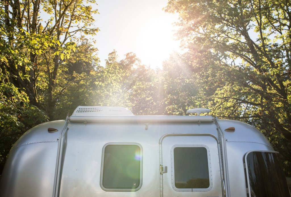 airstream camper backlit with sun streaming thru trees