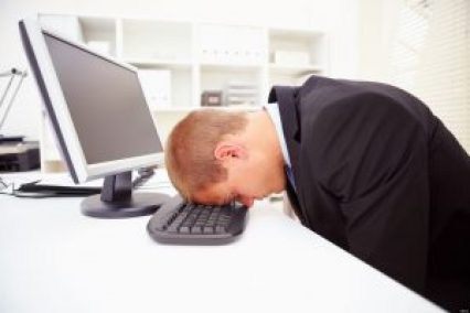 C4NPMK Portrait of a stressed businessman with his forehead resting on the computer keyboard