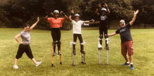 Three kids stand on stilts supported by two Airhedz staff members.
