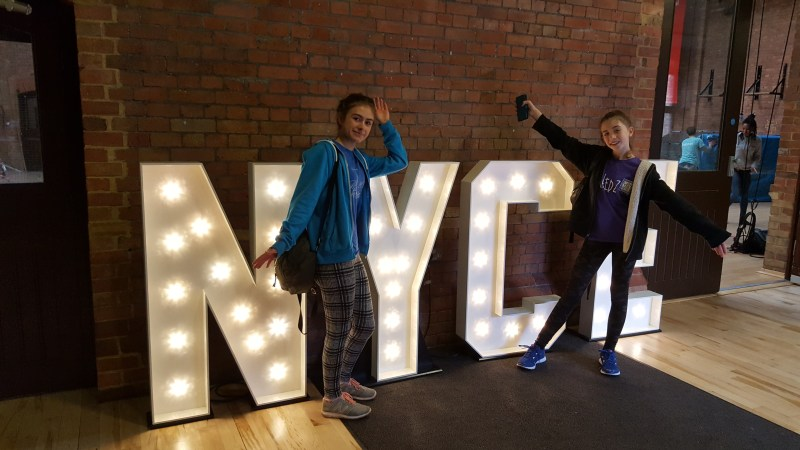 Two young women stand in front of large lights spelling out: NYCE