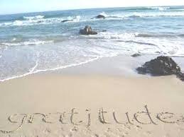 Gratitude written in sand on the beach.