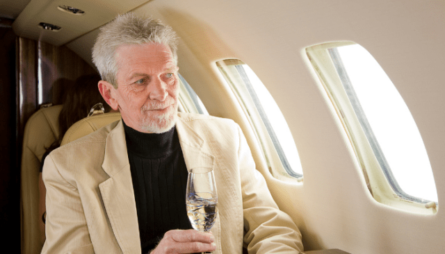 Older man on private jet with champagne