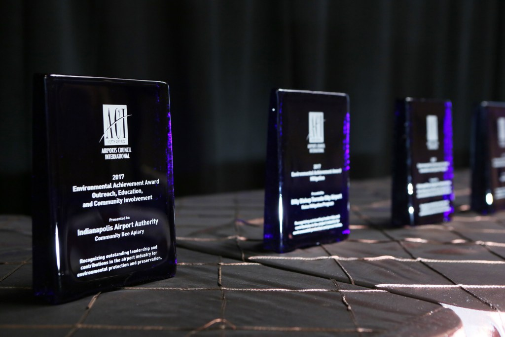 ACI-NA's Environmental Achievement Awards glass awards in a row on a table
