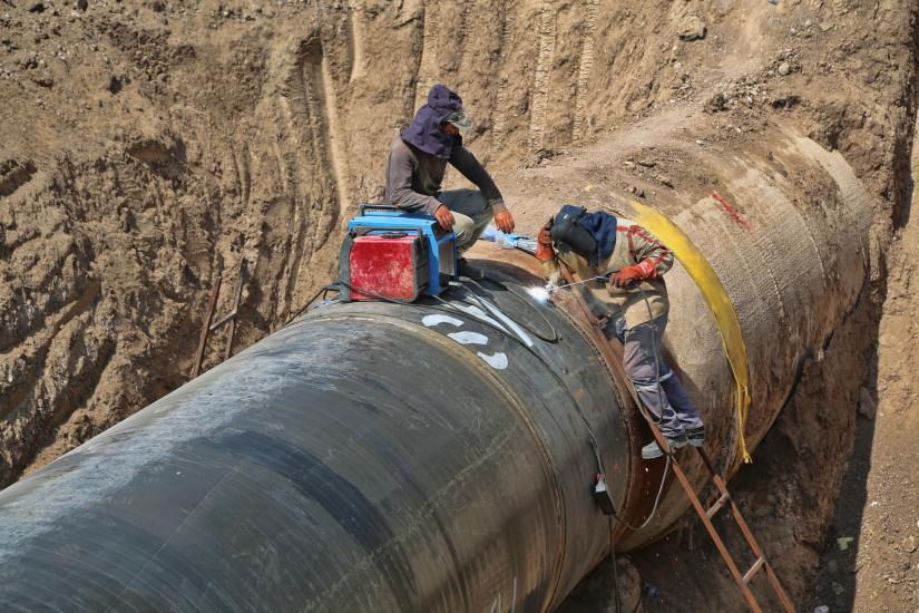 Two workers welding sections of a pipeline together