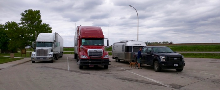 airstream next to semis at a truckstop