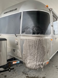 the Airstream covered in road snow