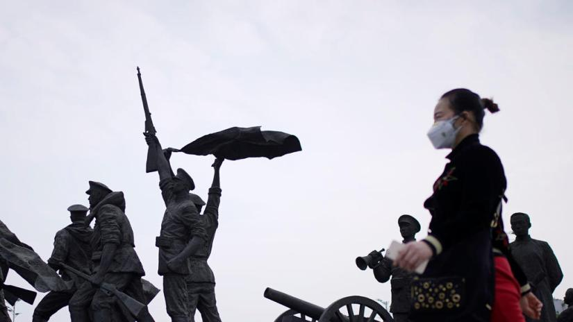 A resident wearing a face mask walks past statue symbolizing Xinhai Revolution, a revolution that toppled China's last emperor in 1911, in Wuhan, Hubei province, the epicenter of China's coronavirus disease (COVID-19) outbreak, April 6, 2020. REUTERS
