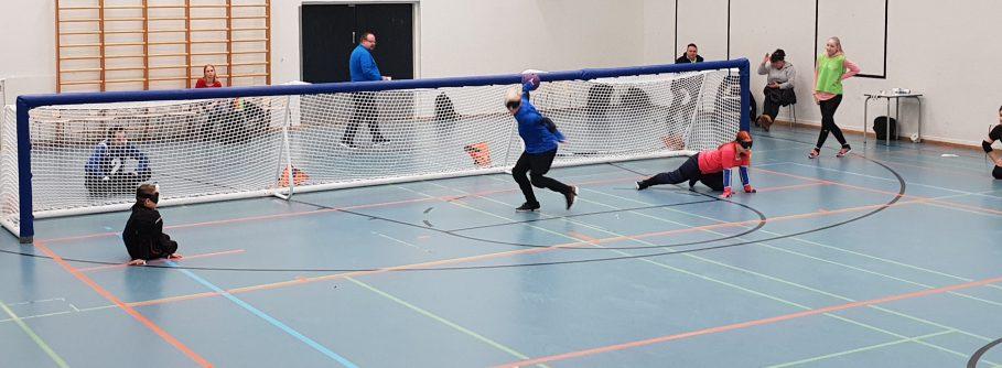 Kuva Aisti Juniors Cup -turnauksesta keväältä 2019. Kuvassa nuori poika ja tyttö seuraamassa laidoilta, kun pelikaveri heittämässä palloa.
