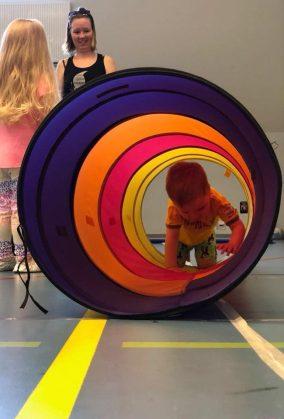 Muutaman vuoden ikäinen lapsi ryömii temppuradan tunnelin läpi kohti kameraa.
