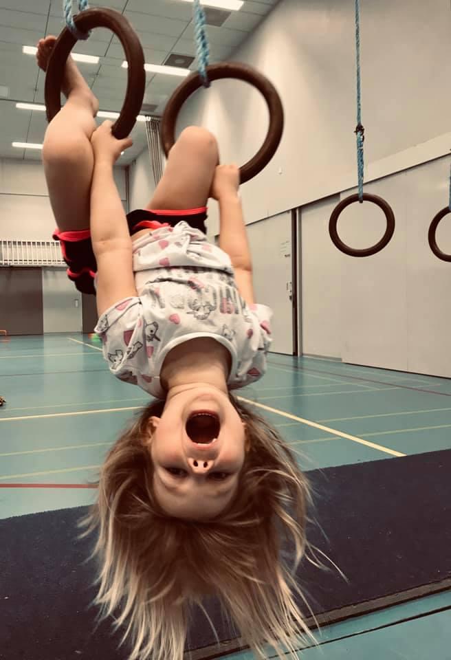 Naurava alle kouluikäinen lapsi roikkuu telinevoimistelurenkaista hiukset hulmuten.