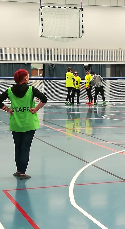 Kuva kotimaisesta turnauksesta, jossa etualalla vapaaehtoinen maalituomari staff-liivi yllään. Taustalla Aistin joukkue aikalisällä.