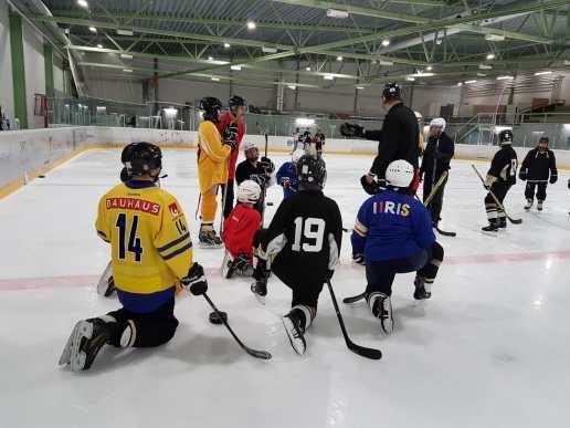 Harjoitustilannekuva, jossa osa pelaajista polven varassa, osa seisaaltaan kuuntelemassa valmentajan ohjeistusta.