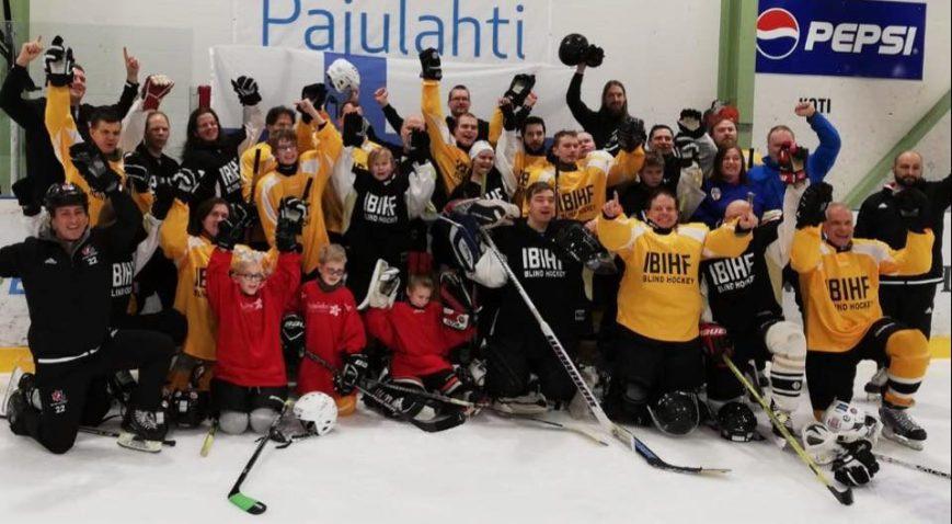 Tuulettava ja iloinen ryhmäkuva jääkiekkokaukalosta, jossa koko vuoden 2020 leiriporukka poseeraamassa.