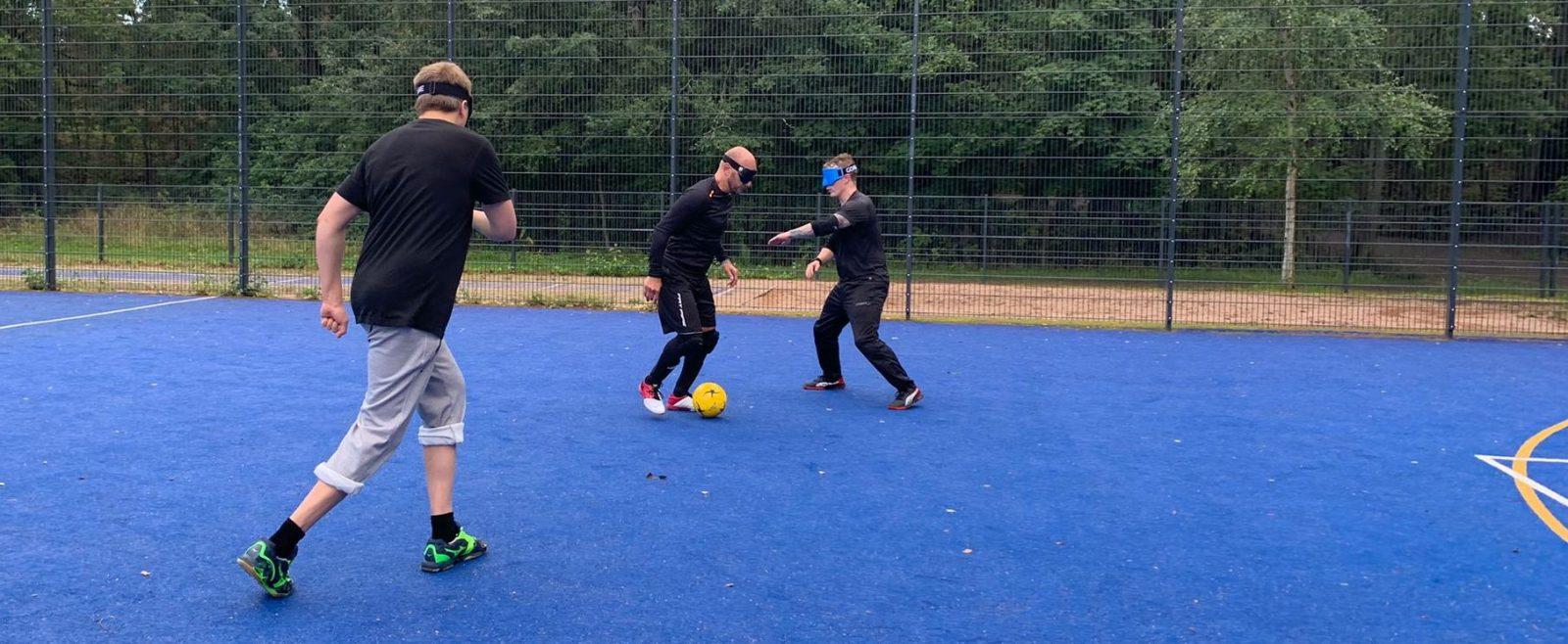 Pelitilannekuva näkövammaisjalkapallosta. Pelaaja etenee pallon kanssa. Puolustaja on käden etäisyyden päässä vastassa ja toinen pelaaja juoksee etualalla rinnalla.